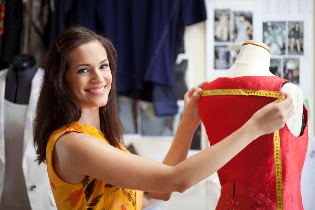 Fashion designer measuring a dress. Shallow depth of field.